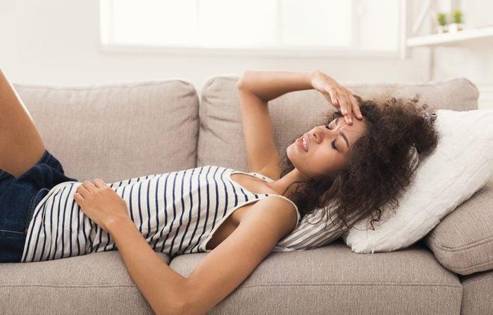 Sad girl with headache lying on sofa at home, copy space