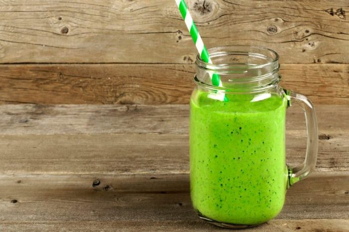 green smoothing with straw in jar-like glass with handle