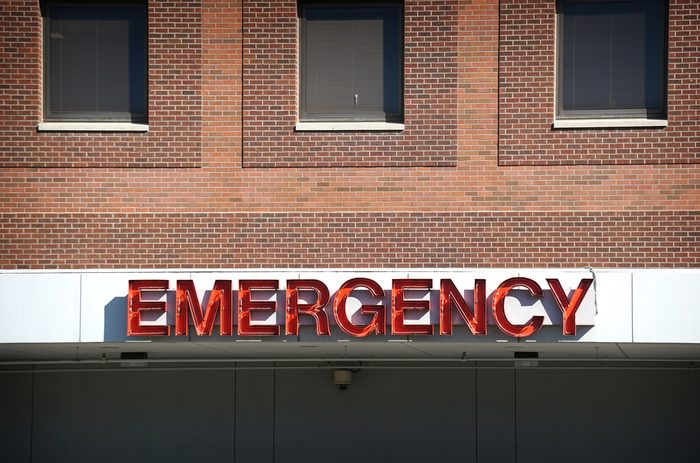 aged and worn vintage photo of neon emergency sign on brick hospital sign