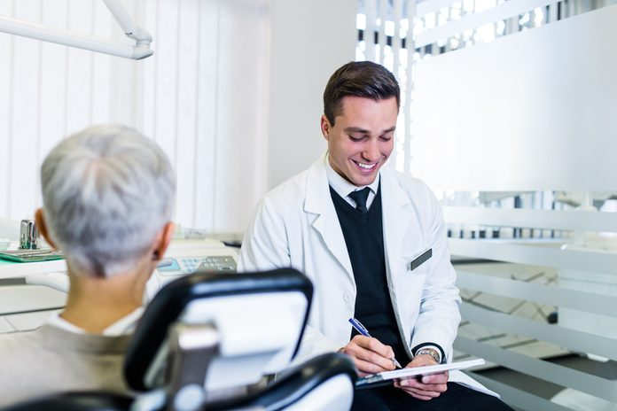 Handsome and attractive male dentist looking at dental x-ray together with his beautiful senior woman patient.