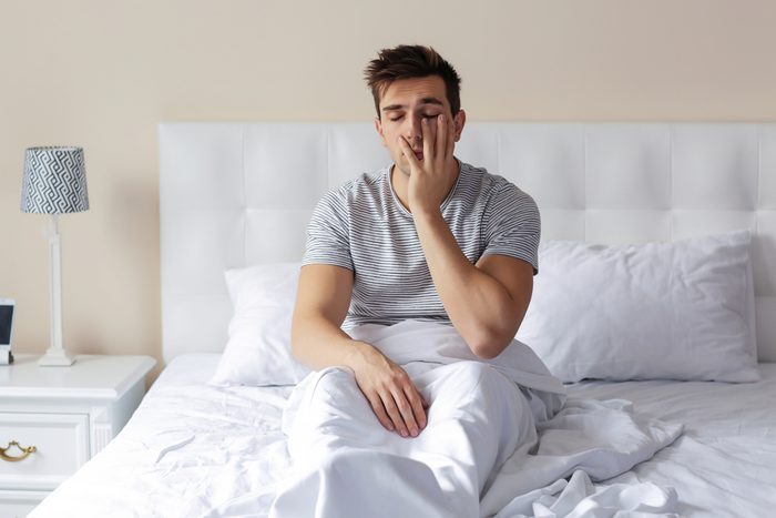 Sleepy young man rubbing his eye in bed at home