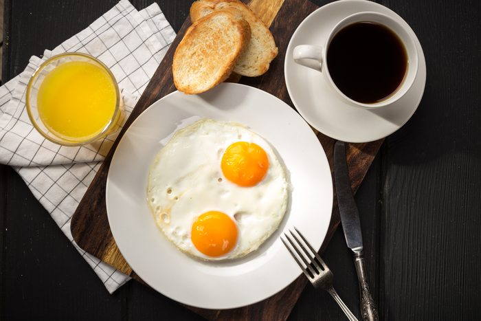 Fried eggs with toasts and coffee on the table