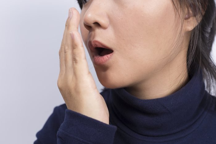 Woman checking her breath with her hand