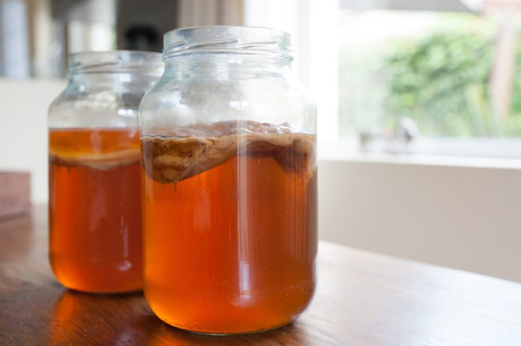 Kombucha tea in jars with the bacteria culture in place to ferment the brew.