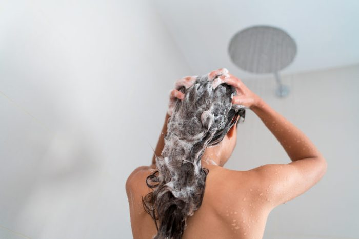 Shower woman washing hair showering in bathroom at home. Unrecognizable person from behind rinsing shampoo and conditioner from her long hair in warm bath with modern ceiling rain water nozzle head.