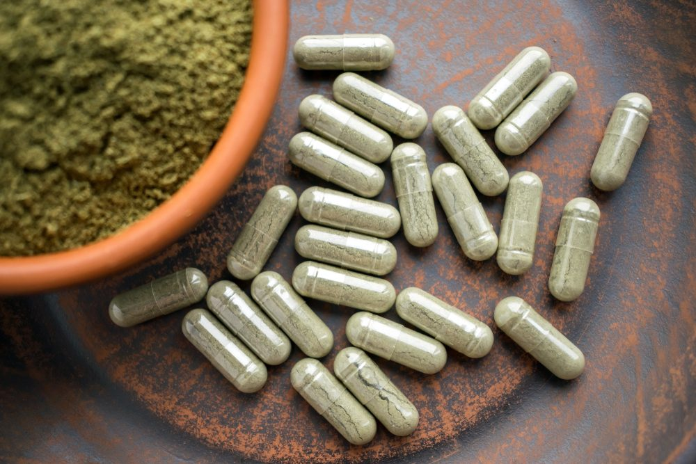 Bowl of green powder surrounded by green capsules