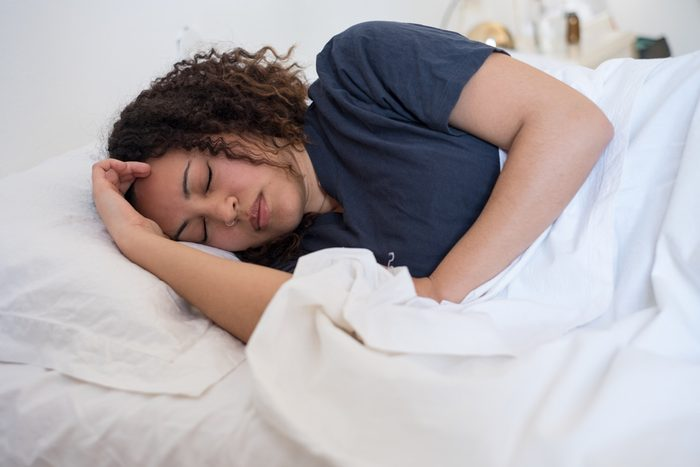 Black woman lying in her bed trying to sleep