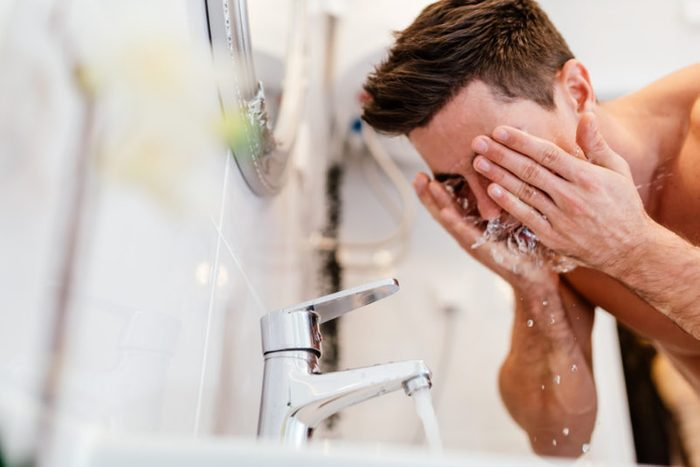Man washing face in morning and practicing hygiene