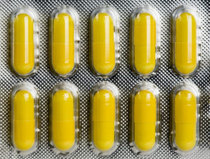 Packing of yellow medical pills background.