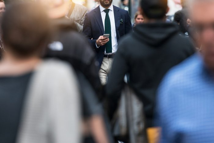 Business people walking from the job in busy city street. Elegant businessman in the people crowd walking and texting on the phone.