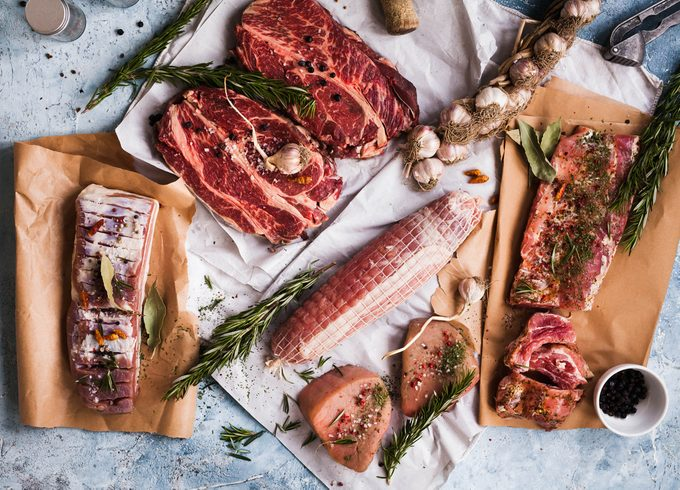 Pork meat raw. Assorted of pork meat with garlic hanging. Raw Pork meat. Assortment of raw pork meat.