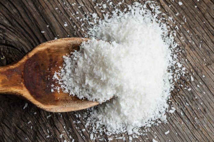 Grounded coconut flakes with wooden spoon