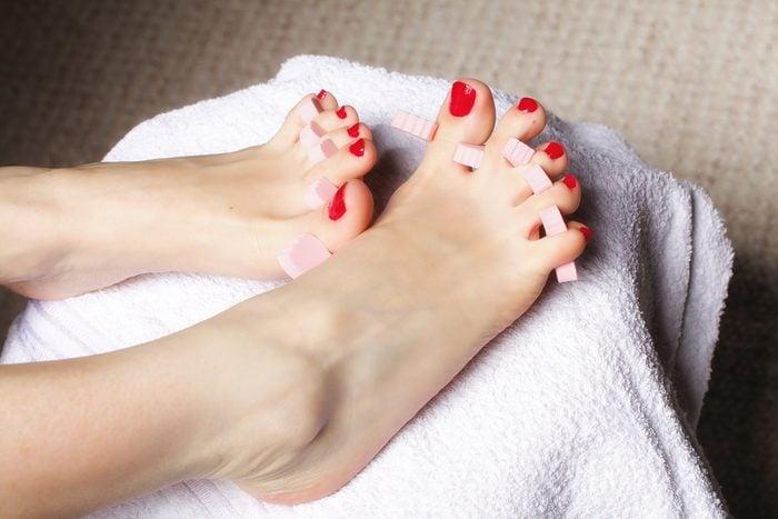 toe separators on woman's feet getting a manicure