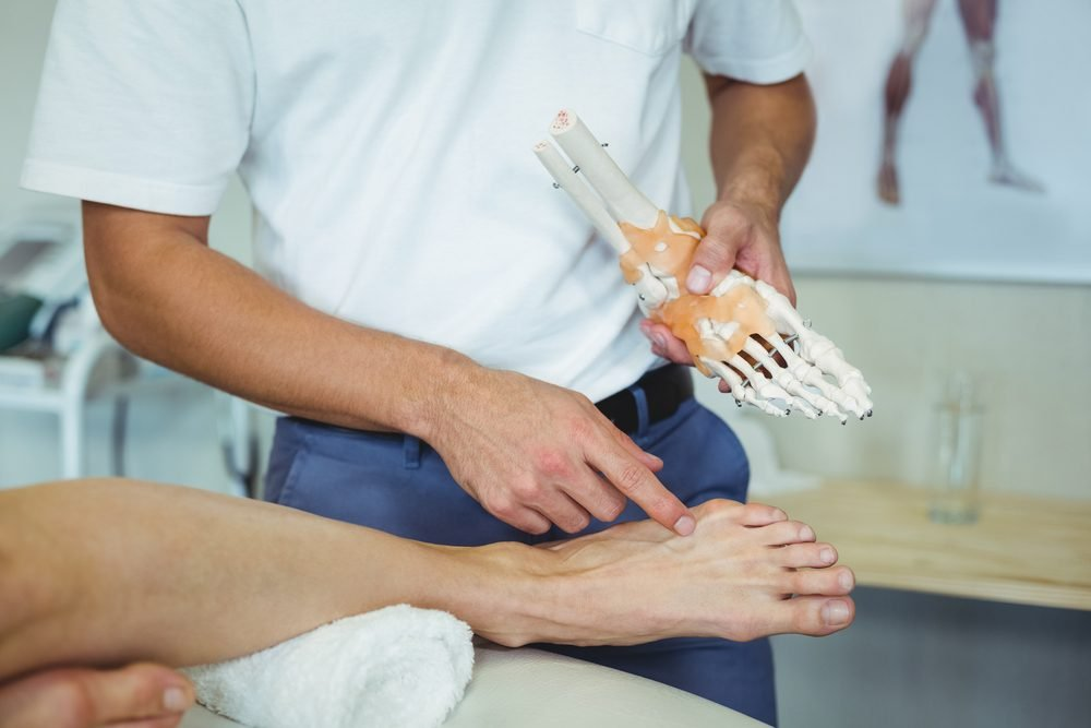 doctor with anatomical foot model and patient's foot