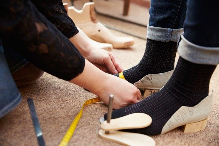 Shoemaker measuring customer's feet, close up