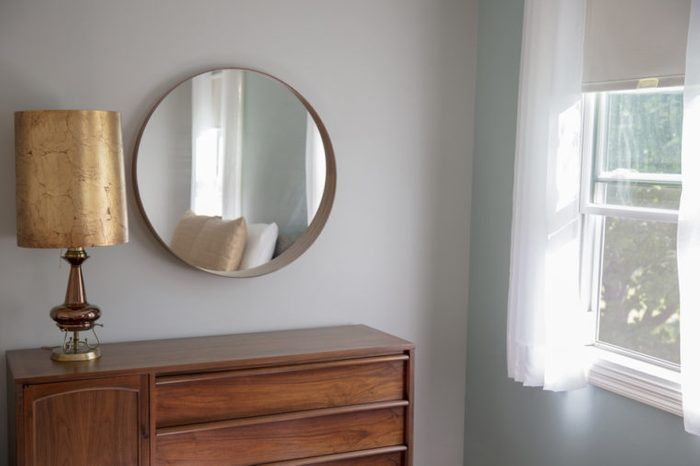 Corner of a mid-century modern bedroom with grey walls, circular mirror, a teak dresser, and a fantastic retro gold lamp.