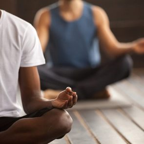 Young black man and a group of young sporty people practicing yoga lesson, sitting in Sukhasana exercise, Easy Seat pose, working out, indoor close up focus on mudra gesture, studio room