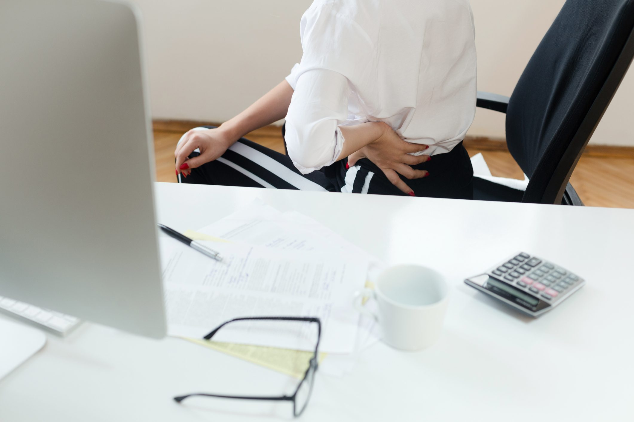 woman with back pain sitting at desk