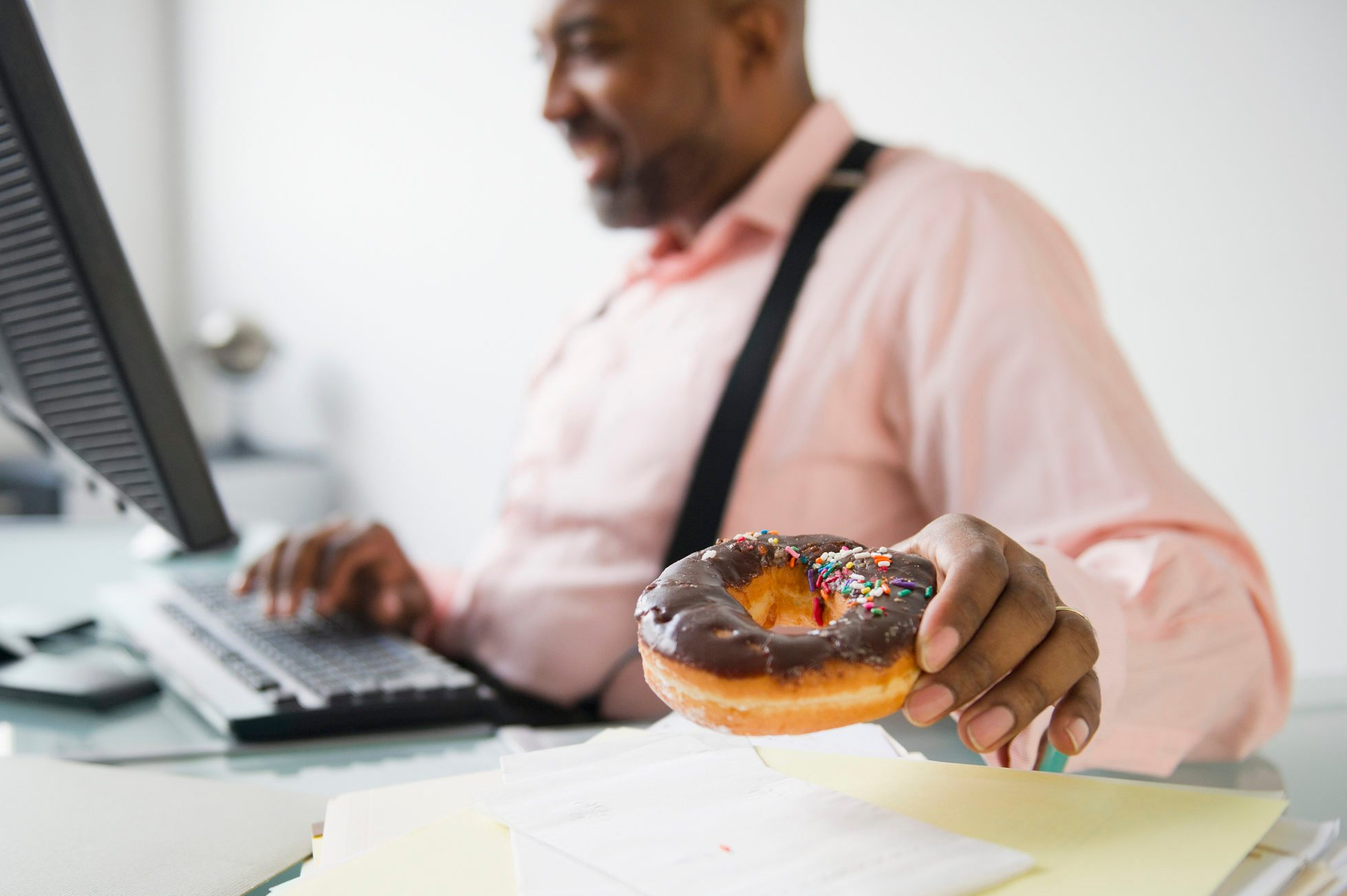 man eating a donut while sitting at desk working