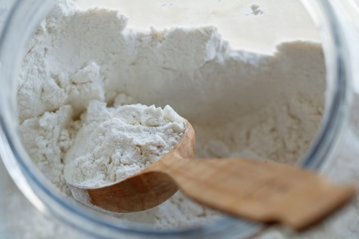 flour in jar with wooden spoon from above