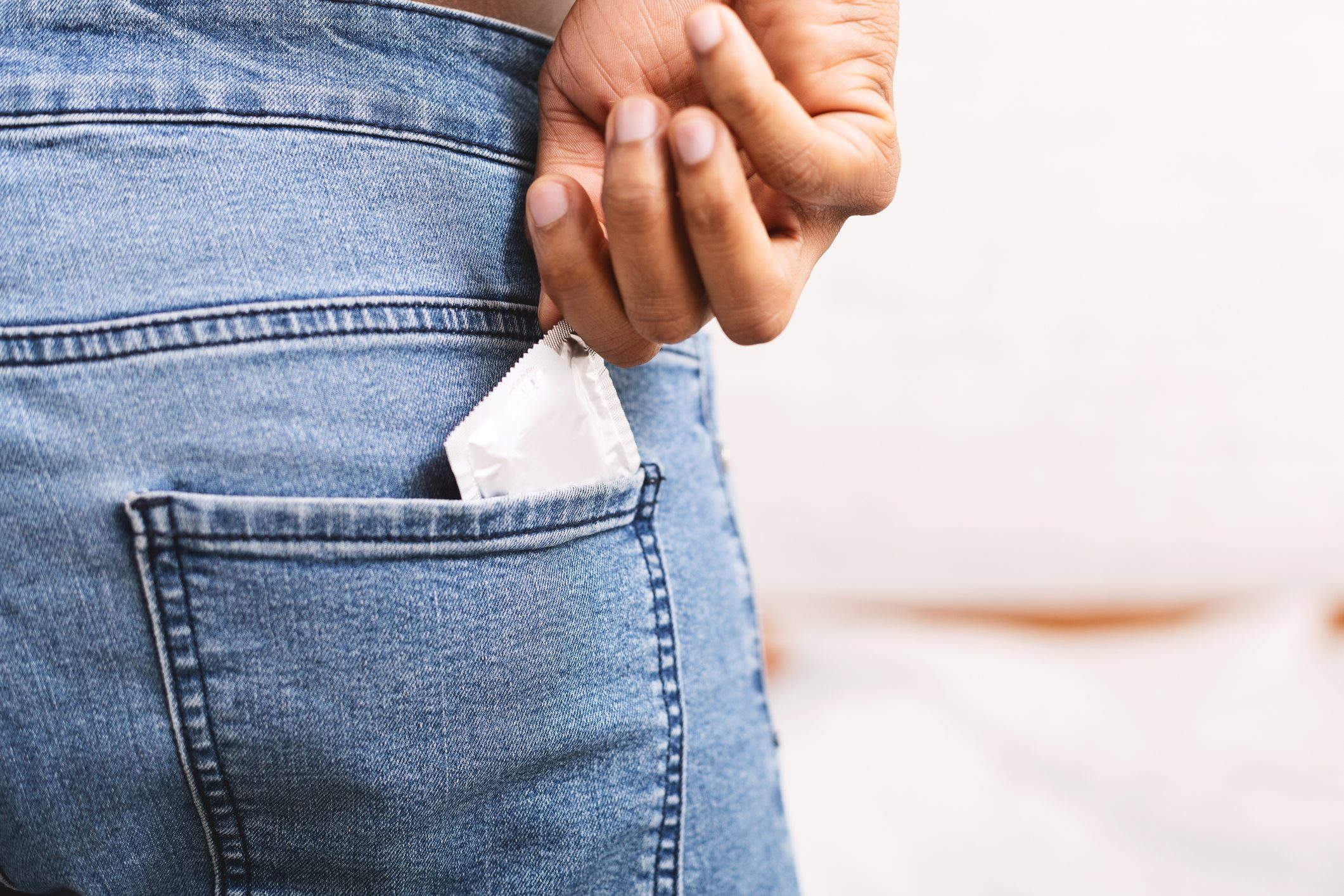 close up of condom in woman's back jean pocket