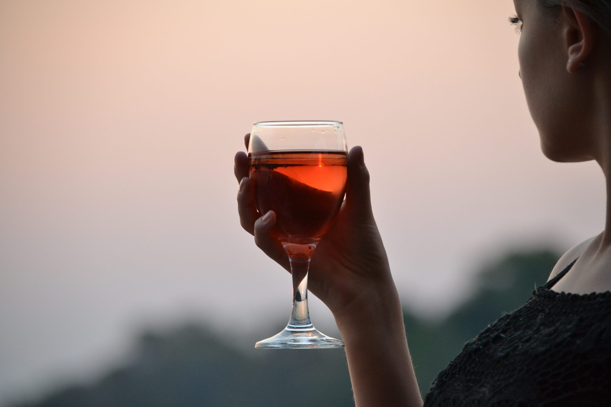 cropped shot of woman drinking wine at sunset