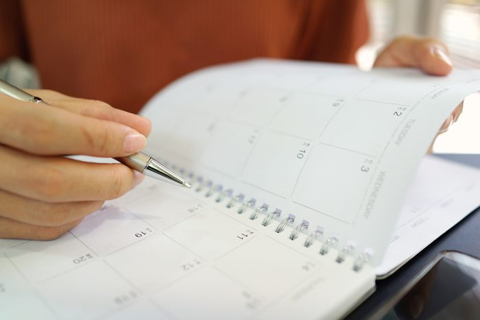 close up of woman holding pen to personal calendar