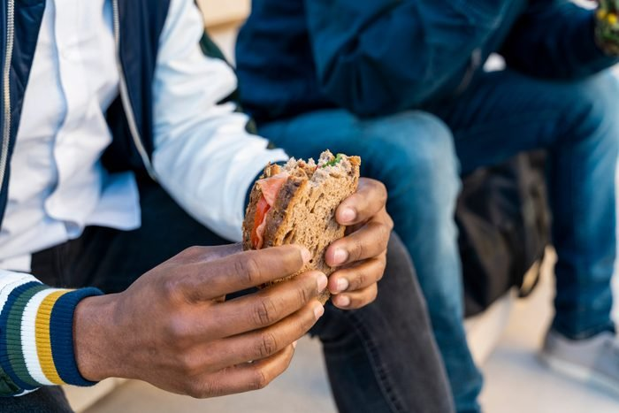close up of man holding a sandwhich