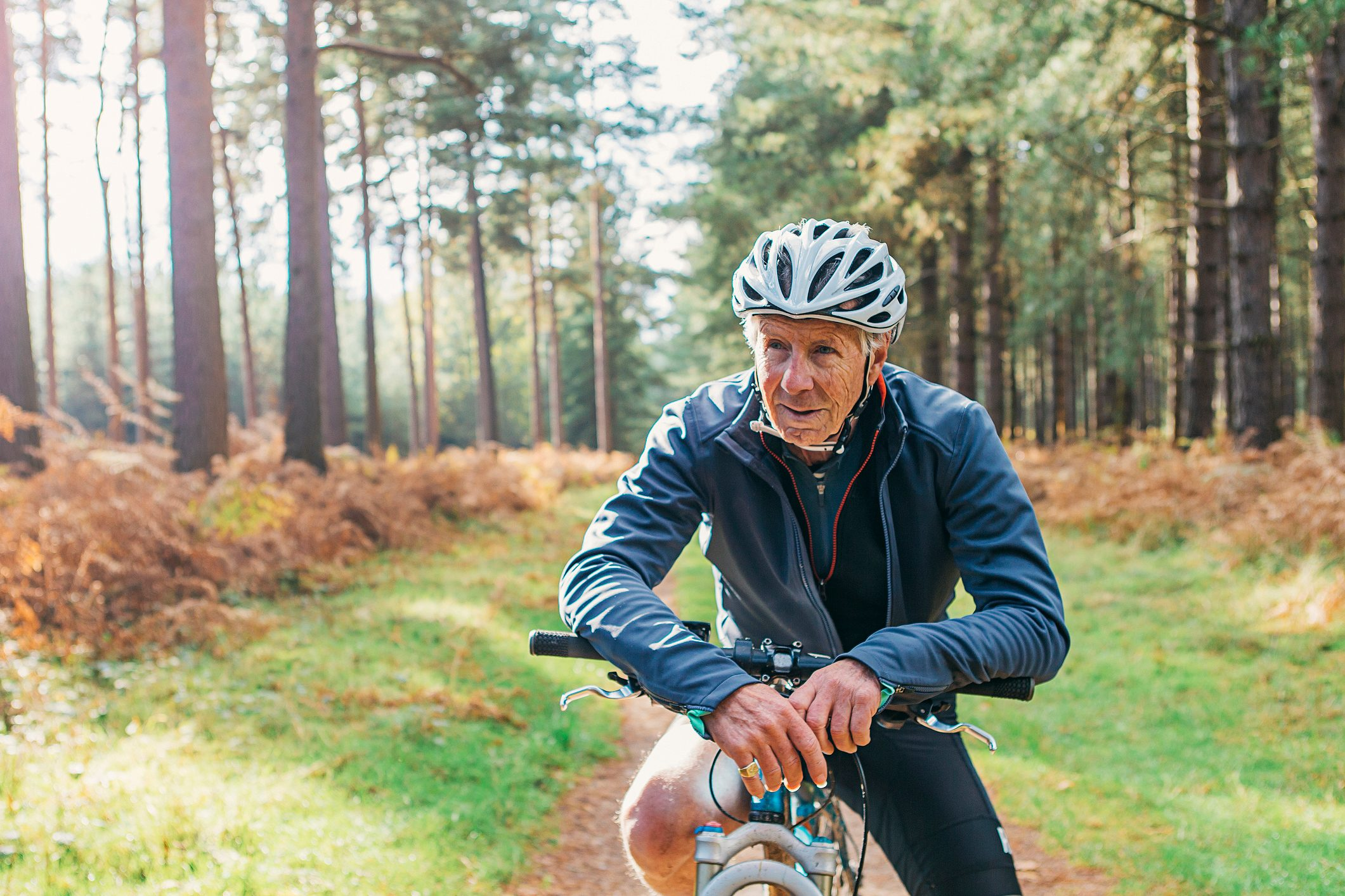 senior man riding bike through forest