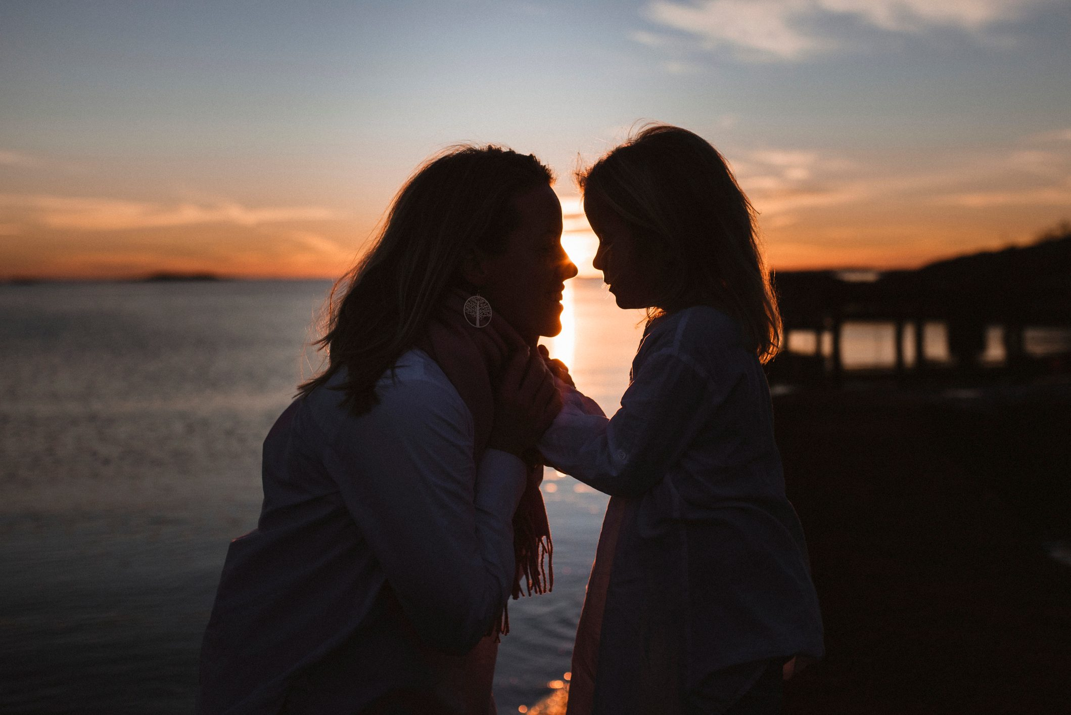 mother and daughter looking at each other with sunset in background