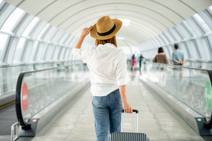 rear view of woman walking through airport holding suitcase