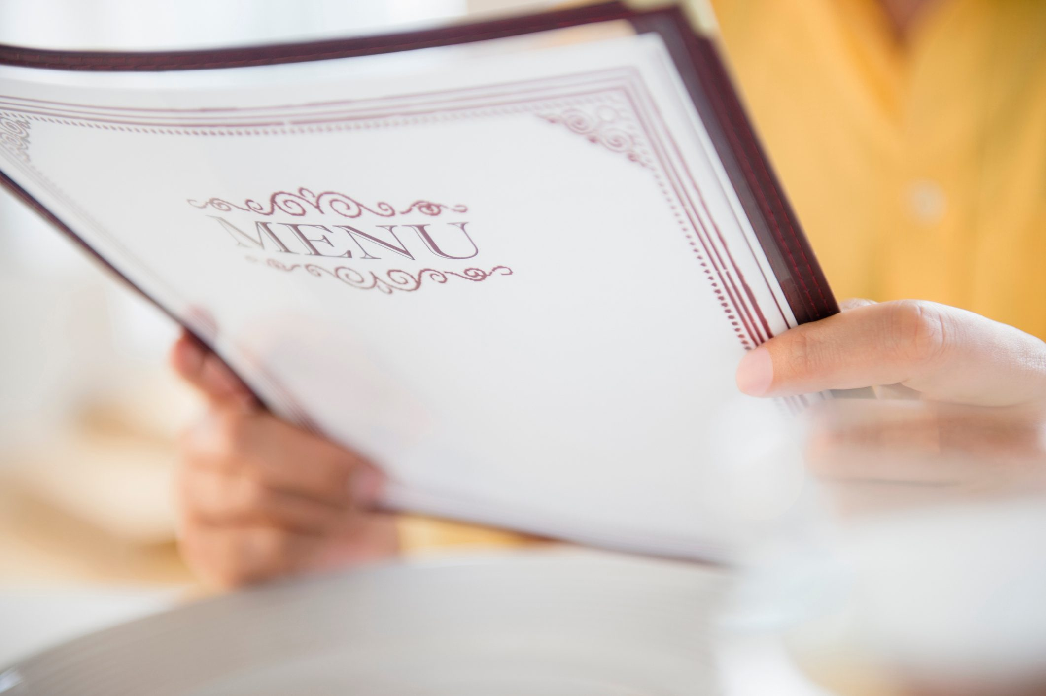 close up of person holding menu at restaurant