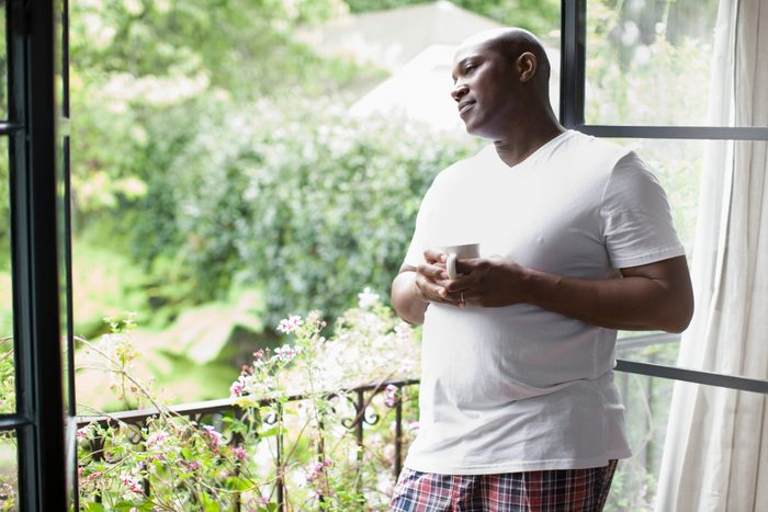 man looking out window drinking coffee in the morning