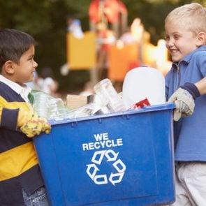 two little boys carrying a blue recycling bin