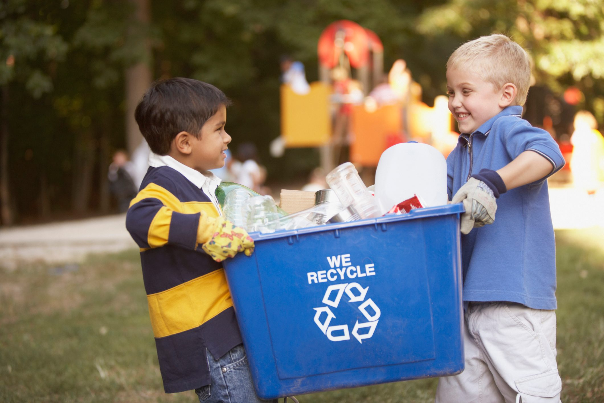 two little boys carrying a blue recycling bin