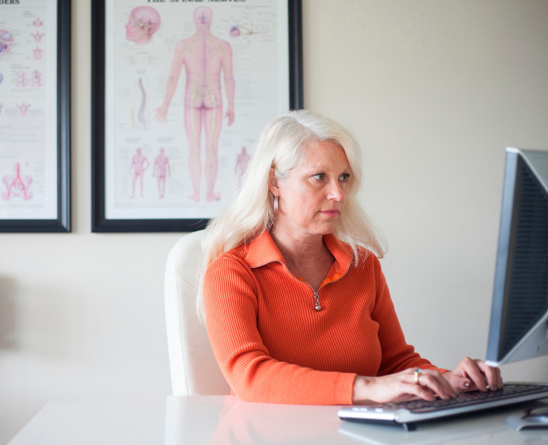 chiropractor working at desk computer
