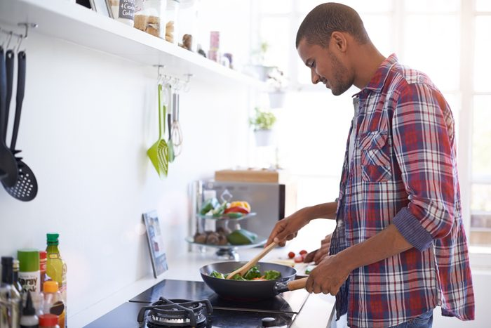 man cooking a meal in kitchen