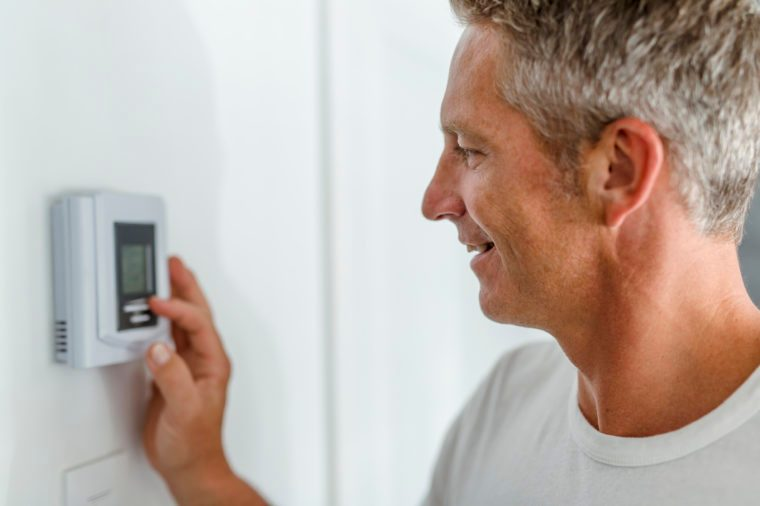 man adjusting the thermostat at home