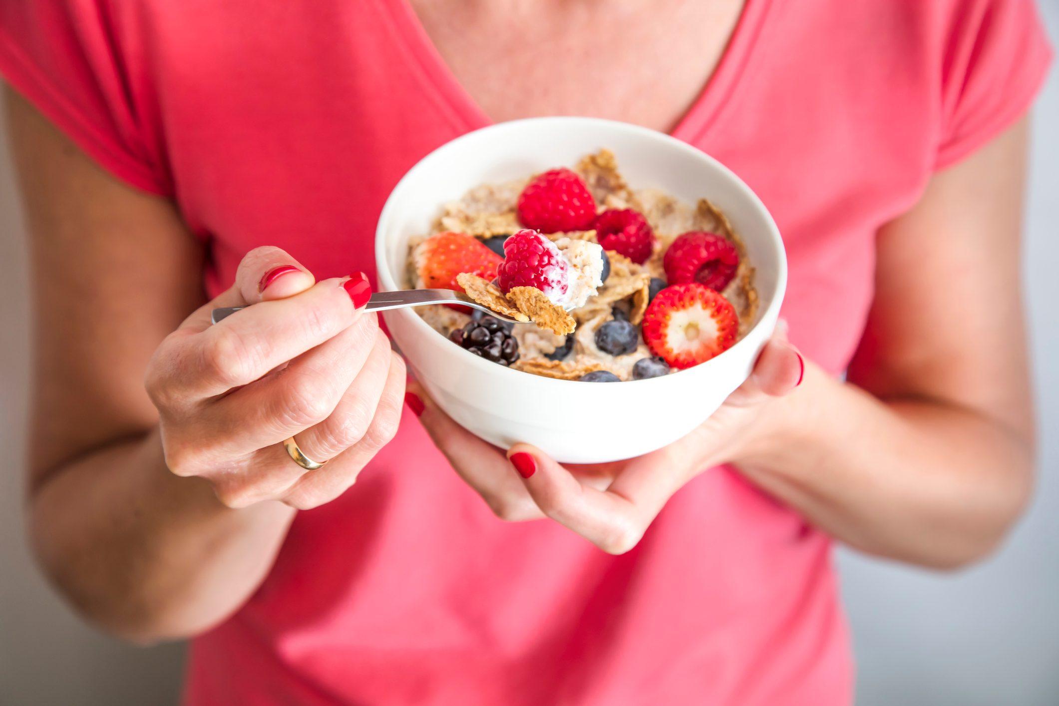 close up of woman holding bowl of yogurt breakfast
