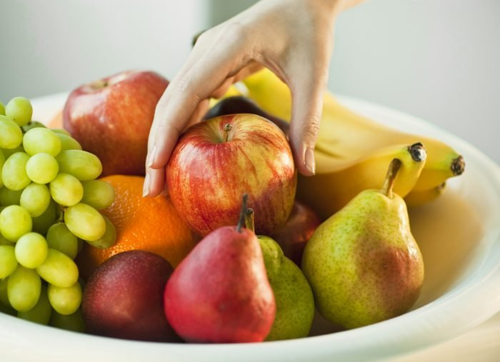 bowl of fruit close up of hand picking up red apple