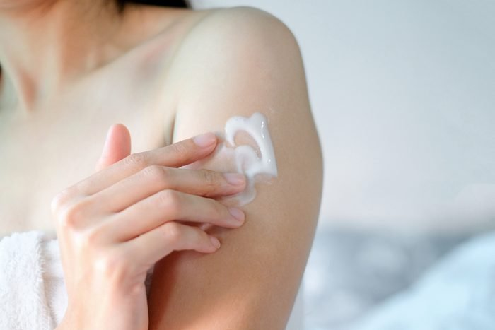 Woman applying moisturizing cream on Arm
