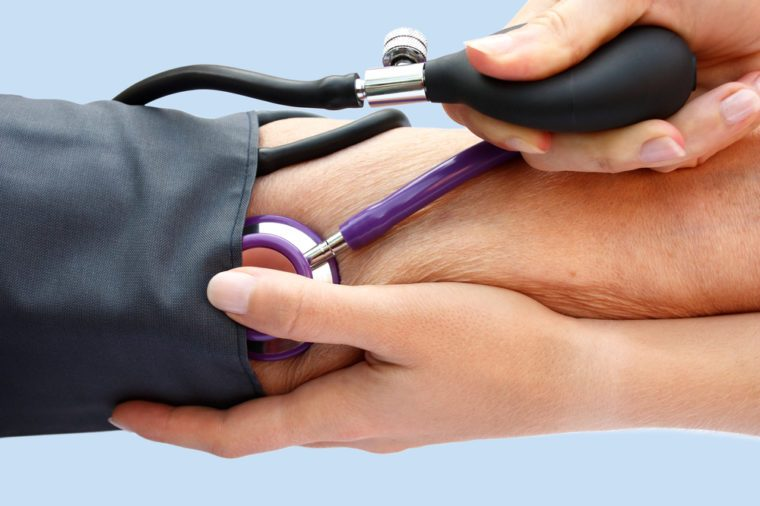 Doctor measuring a person's blood pressure with a cuff.