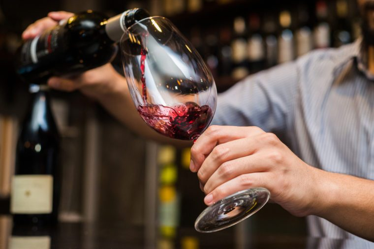 Waiter pouring red wine in a glass.
