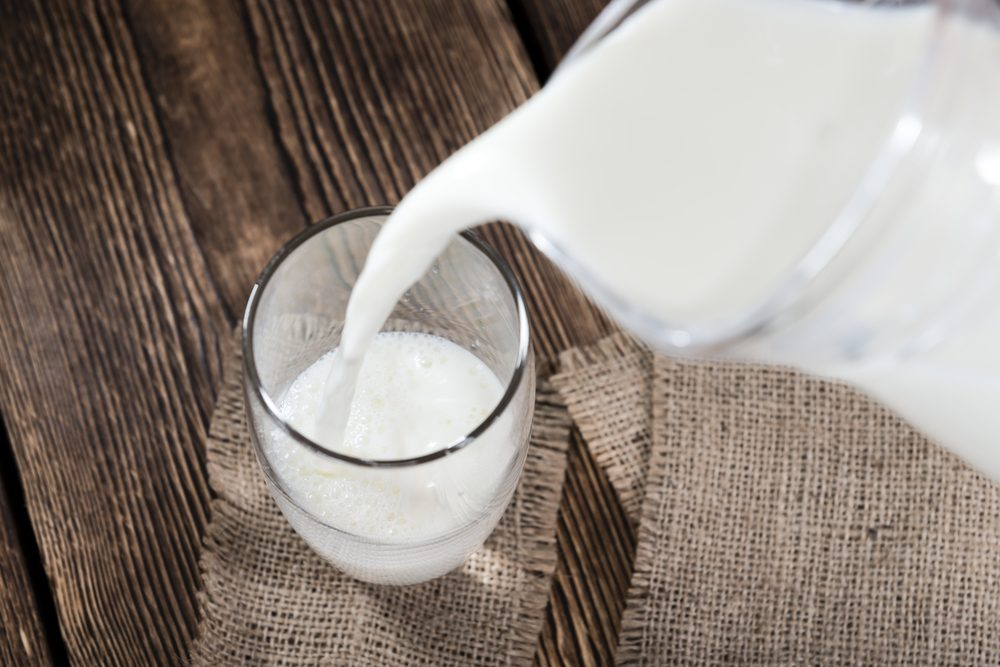 Portion of Milk on a dark wooden background (close-up shot)