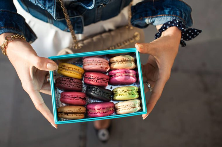Woman holding box with colourful macaroons.