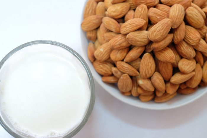 Almond milk in glass with almonds on white background