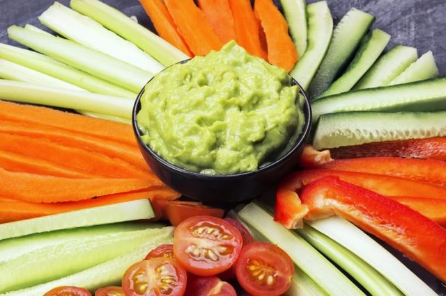 bowl of guacamole surrounded by sliced veggies