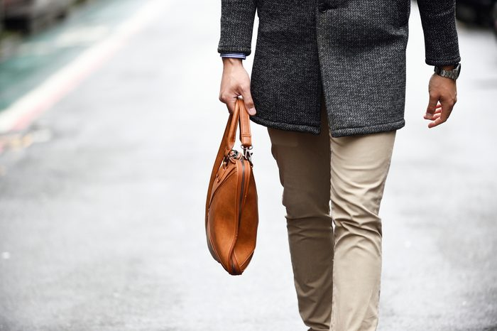cropped shot of man holding man purse