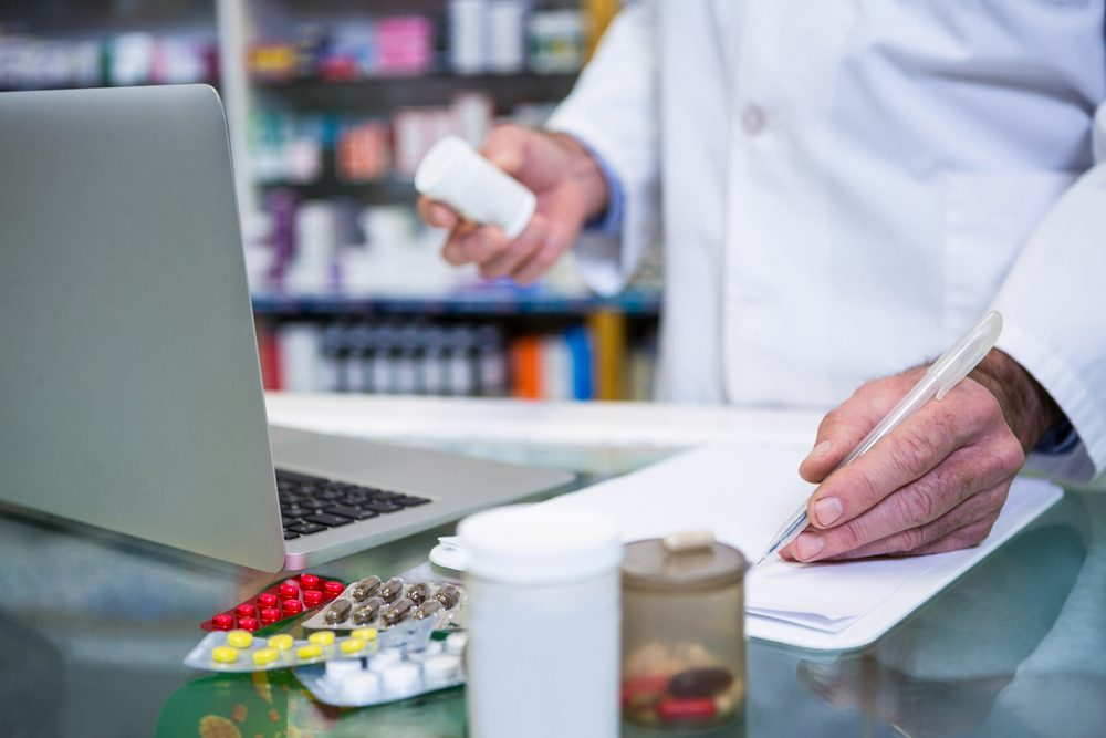 pharmacist with pill bottle on computer