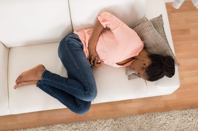 woman curled up in fetal position on a white couch